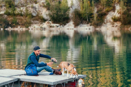 Man dog owner and friend beagle dog on the wooden pier on the mountain lake and enjoying the landscape during their walking in the autumn season time. Male pouring a tea, but dog had seen sth in water