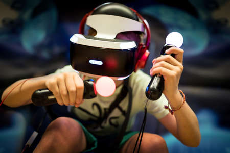 Young teenager boy using a Virtual reality headset with goggles and hands motion controllers in playing game zone. Modern technologies concept image. Standard-Bild