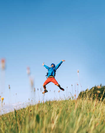 Backpacker traveler emotionally jumping over green grass mountain meadow with backpack with wide opened arms and legs. Human's freedom in nature concept image. Standard-Bild