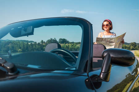 Woman looking a right road in the roadmap during her auto travel in the convertable cabriolet car. Traveling and navigation concept image. Standard-Bild