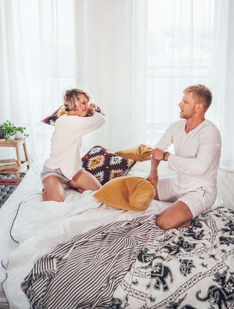 Laughing blonde hair young adults couple in pajamas having a pillow battle on cozy bed in the bedroom. Couples relationships concept image. Standard-Bild