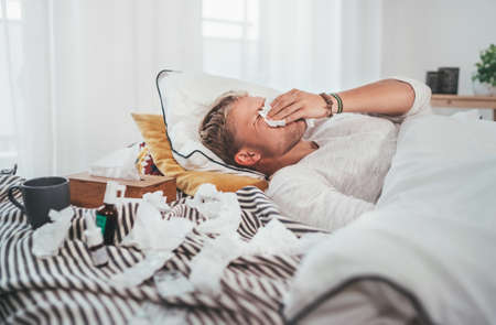 Unhealthy and tired man sneezing or wiping snotty nose man lying in a cozy home bed beside a lot of used paper tissues and medicines on the blanket. Season virus flu and home quarantine concept image.