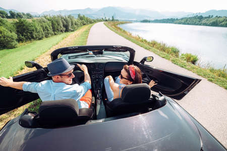Couple in love getting into the convertable auto and starting a trip. Couple honeymoon or vacation concept image.