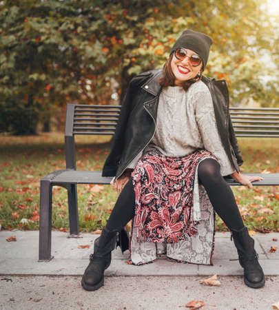 Sincerely laughing female dressed fashion boho style colorful long dress, warm knitted sweater with black leather biker jacket and Beanie Hat with flap bag sitting on bench at autumn city park