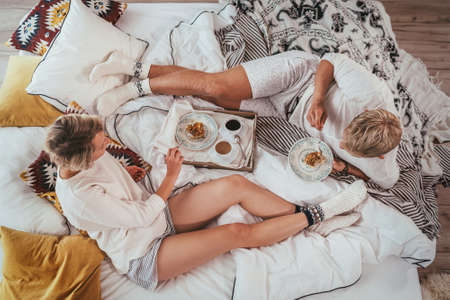 Top view of the couple in pajamas lazy relaxing lying in cozy bed in bedroom and having a morning coffee with apple pie dessert. They carefree peacefully chatting.  Couples relations concept image.