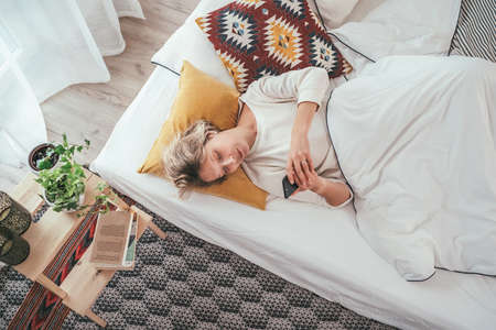 Young blonde female dressed pijama lying in the cozy bed under the blanket and browsing a smartphone internet. Sweet cozy home and wireless technology concept image. Standard-Bild