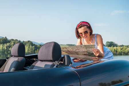 Happy sincerely smiling woman looking a right road in the roadmap during her auto travel in the convertable cabriolet car. Traveling and navigation concept image. Standard-Bild