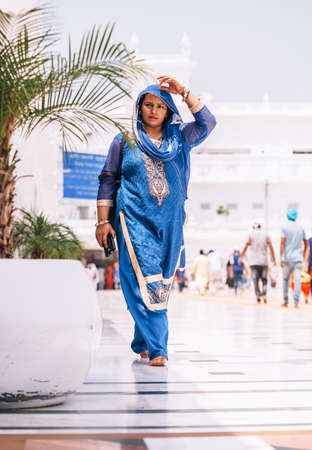 Amritsar, India - AUGUST 15: Portrait of indian woman dressed in female traditional sari (saree) garment walking by the Golden Temple (Harmandir Sahib) on August 15, 2016 in Amritsar, Panjab, India.