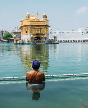 Sikh pilgrim praying in  holy tank near Golden Temple (Sri Harmandir Sahib), Amritsar, INDIA Standard-Bild