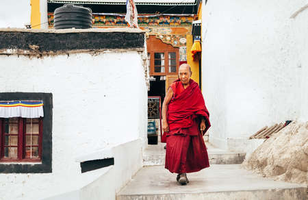 Thiksay Monastery in Thiksey village, India – August 20, 2016: Aged monk goes by the monastery weared in traditional red kasaya  in Thiksey village, India