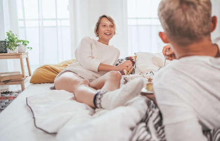 Laughing blonde hair young adults couple in pajamas lazy relaxing lying in a cozy bed in the bedroom and having a peacefully carefree chatting. Couples relations concept image. Standard-Bild