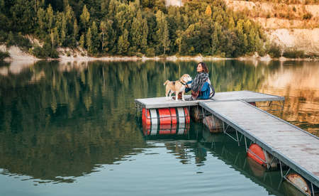 Woman dog owner and his friend beagle dog on the wooden pier on the mountain lake during their walking in the autumn season time. Walking in nature with a pet concept image.