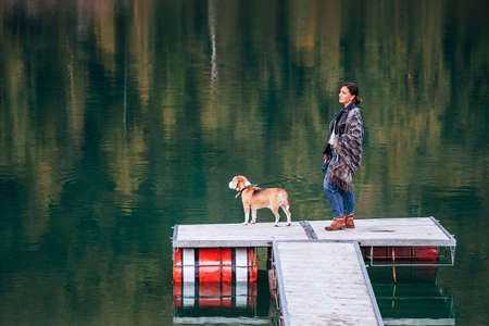 Female dog owner and his friend beagle dog on the wooden pier on the mountain lake during their walking in the autumn season time. Walking in nature with a pet concept image. Standard-Bild