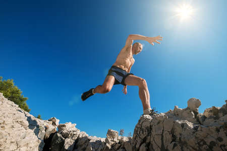 Sky runner with sweaty muscular body running in mountain and jumping over the cleft cliff during the morning jogging. Active sporty people activities wide-angle concept image.