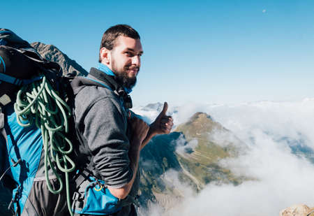 Smiling bearded climber with huge backpack with climbing rope showing thumb sign enjoying a French Apls valley with picturesque clouds near Nid d'Aigle at 2362m during Mont Blanc ascending, France Standard-Bild