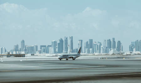 Doha, Qatar - January 2, 2018: Qatar Airways aircraft with downtown skyscrapers on the background arriving in Doha capital city in Hamad International Airport, Doha, Qatar.