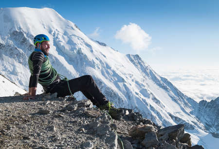 Bearded Climber in a safety harness, helmet, and on body wrapped climbing rope with sitting at 3600m altitude with picturesque Aiguille de Bionnassay mountain during Mont Blanc France route