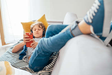 Preteen boy lying at home on cozy sofa dressed casual jeans and new sneakers listening to music and chatting using wireless headphones connected with smartphone. Child use electronic devices concept