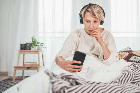 Young female sitting on cozy bed dressed pajamas browsing the internet and listening to music using wireless headphones. Music playing modern technology and free time spending concept Standard-Bild
