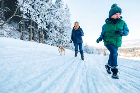 Mother and son having a fun. They running with their beagle dog in snowy forest during dog walk. Mother and son relatives and femily values concept image. Standard-Bild