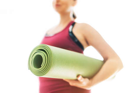 Young Woman holding rolled gymnastic yoga rubber mat on the white background light starting morning yoga exercises. Active people and healthy lifestyle concept.