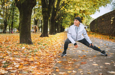 Fit athletic woman doing workout before jogging in the autumnal city park on the kids playground. Young fitness female runner stretching legs while warming up. Active runners people concept image.