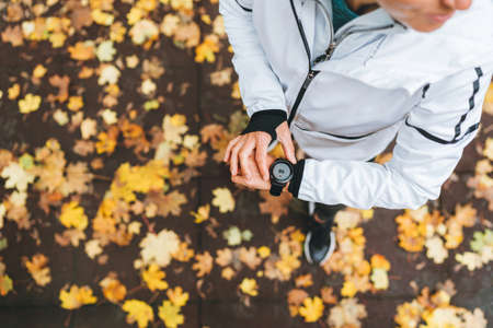 Caucasian female runner starting activity on smartwatch. Woman monitoring a heart rate on her watch outdoors. Top view with yellow leaves background. Running people and modern devices concept image. Standard-Bild