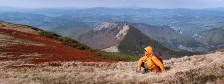 Dressed bright orange jacket backpacker with trekking poles sitting on the hill enjoying green valley at Mala Fatra mountain range, Slovakia. Active people and European hiking tourism concept image.