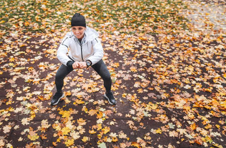 Fit athletic smiling woman dressed sporty clothes doing squatting exercises in the autumnal city park on the playground covered with yellow leaves. Active lifestyle people in the city living concept.