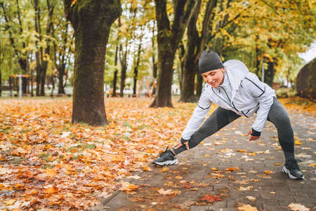 Fit athletic woman doing workout before jogging in the autumnal city park on the kids playground. Mid aged fitness female runner stretching legs while warming up. Active runners people concept image.