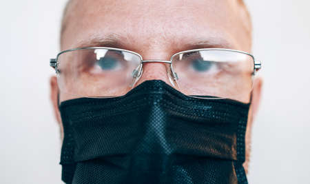 Portrait of man in misted glasses and black facial mask during a COVID-19 world pandemic looking at camera. Virus self-protection and vision health concept image.