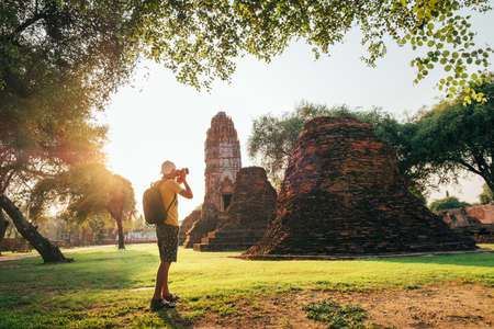 Tourist traveler with a backpack taking a photo of ancient Wat Ratchaburana Buddhist temple in holy ancient Ayutthaya city, Thailand