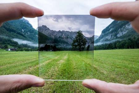 Professional photographer holding ND Gradient Filter glass appreciating an effect. Logar valley, Slovenia. 免版税图像