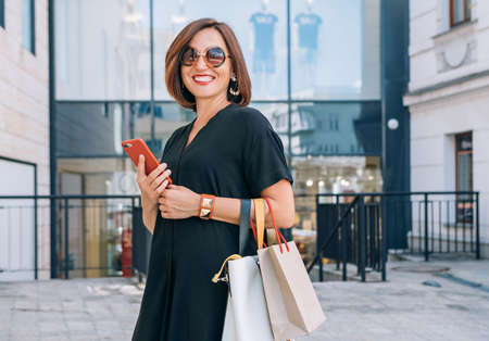 Smiling beautiful modern middle-aged female Portrait dressed black dress and sunglasses with shopping bags holding slim smartphone cheerfully smiling at the camera. Beautiful people concept image.