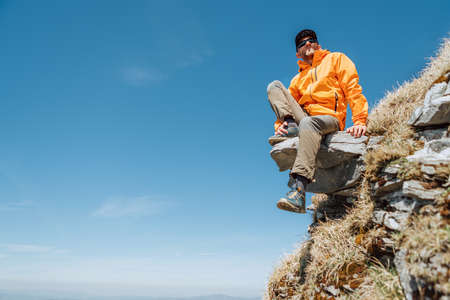 Dressed bright orange jacket hiker in a baseball cap and sunglasses sitting on the rocky cliff enjoying green valley at Mala Fatra mountain range, Slovakia. Active people and European tourism concept.