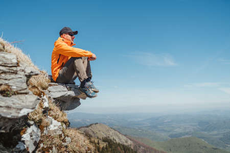 Active people and European tourism concept image. Dressed bright orange jacket hiker in baseball cap and sunglasses sitting on rocky cliff enjoying green valley at Mala Fatra mountain range,Slovakia