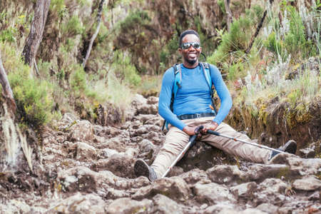 Portrait of a cheerfully smiling African-American Ethnicity young man in sunglasses sitting with backpack and trekking poles and resting on mountain trekking path. Active people and traveling concept 免版税图像