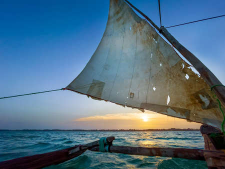 Old traditional maritime traditional vessel Dhow boat sailing under torned sail in the open Indian ocean near Zanzibar island in beautiful sunset, Tanzania. Traveling and unique local culture concept.