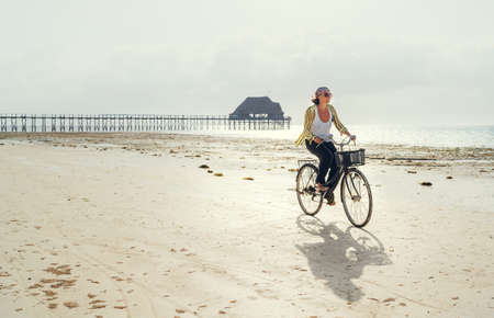 Middle-aged female dressed light summer clothes riding old vintage bicycle with front basket on the lonely low tide ocean white sand coast on Kiwengwa beach on Zanzibar island, Tanzania.