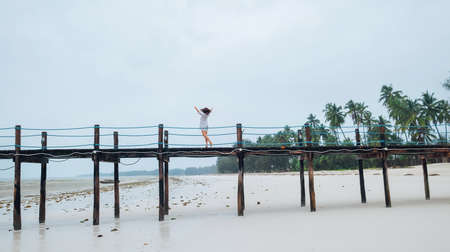 Happy cheerful woman dressed in light summer clothes dancing barefoot on the Zanzibar island low tide sandy beach wooden pier. Careless vacation in the tropical countries concept image