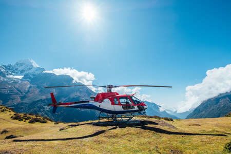 Civil helicopter landed in high altitude Himalayas mountains. Thamserku 6608m mountain on the background. Namche Bazaar, Nepal. Safety air transportation and travel insurance concept image. 免版税图像