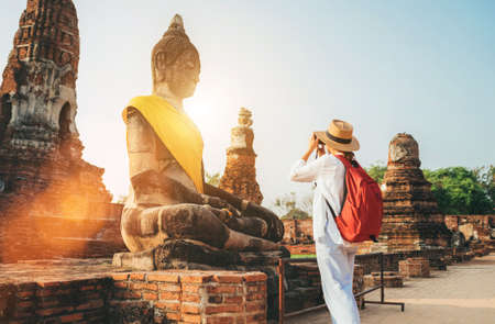 Solo traveler woman with a backpack taking a photo of Seated Buddha Statue at Wat Ratchaburana or Wat Ratburana Buddhist temple in the Ayutthaya Historical Park, Thailand 免版税图像