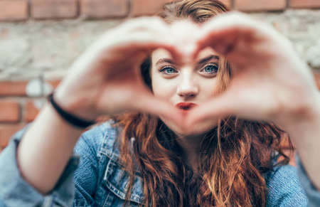 Portrait of red curled long hair caucasian teen girl with applied red lipstick lips with blue eyes on the brick wall background making a heart shape with fingers gesture. Love concept image.