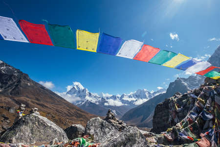 Holy buddhist praying multicolored flags with mantras flapping and waving on the strong wind with valley view and Ama Dablam 6812m peak.Everest Base Camp trekking route near Dughla 4620m.