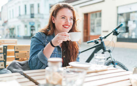Portrait of sad red curled long hair caucasian teen girl sitting on a cozy cafe outdoor terrace on the street and drinking coffee. Young woman taking a break in her city bicycle tour.