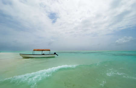 Shallow atoll sandbanks turquoise waves with lonely pleasure boat around Mnemba island in the Indian Ocean near the Zanzibar island, Tanzania. Exotic countries traveling concept image.
