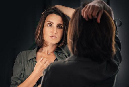 Sensual low key boudoir portrait of seductive female gazing on her mirror reflection as she ruffling hair. Human emotion or fashion concept image.