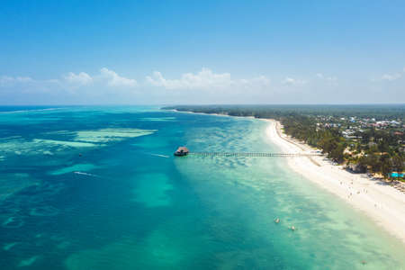 Aerial shot of Kiwengwa beach washed with turquoise Indian ocean waves. White sand sandbank beach on Zanzibar island, Tanzania. Exotic countries travel concept