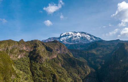 Aerial shot of a highest African continent summit - Kilimanjaro Uhuru Peak 5895m volcano covered with snows. Drone point of view flying up at cca 3600m. Umbwe route, Tanzanian National Park
