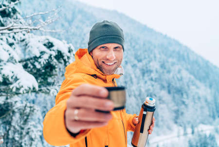 A middle-aged man offering a hot drink cup from a flask dressed in a bright orange softshell jacket while he trekking the winter mountains route. Active people in the nature concept image. 免版税图像
